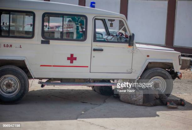 Kashmiri mechanics repair an ambulance outside a hospital on July 12 2018 in Srinagar the summer capital of Indian administered Kashmir India Kashmir...