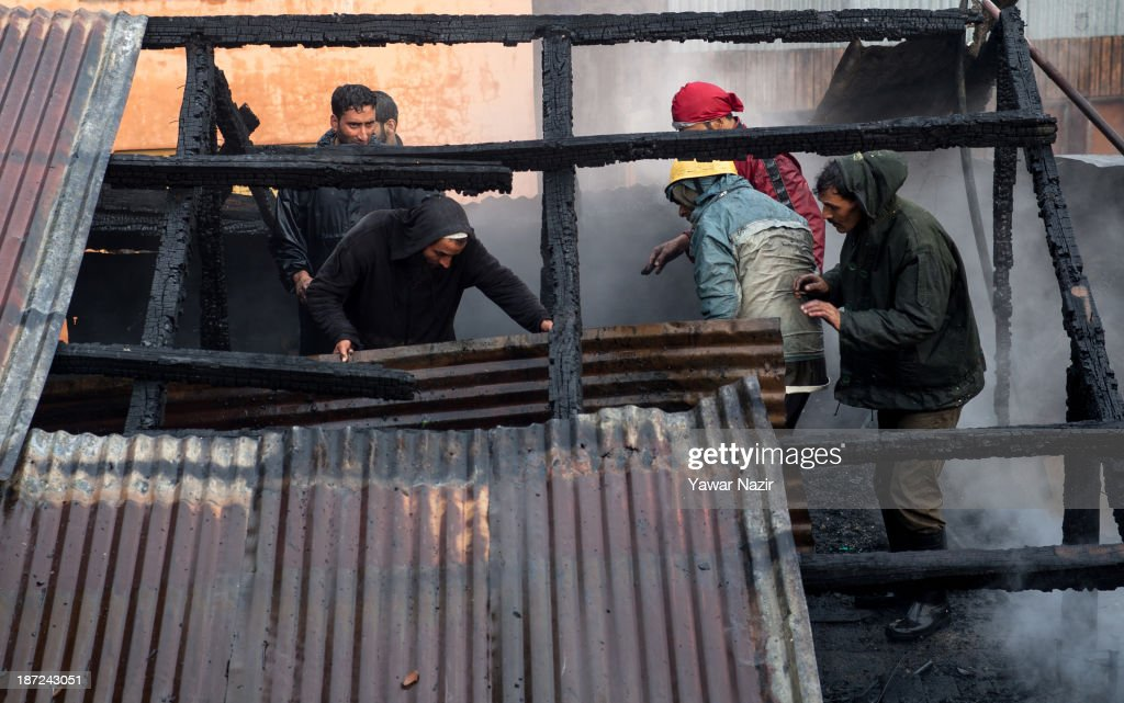Kashmiri men and firefighters work to extinguish a fire that gutted residential houses on November 07, 2013, in Srinagar the summer capital of Indian administered Kashmir, India. Several families were left homeless in Maharaja Bazar locality in uptown Srinagar and no injuries were reported.