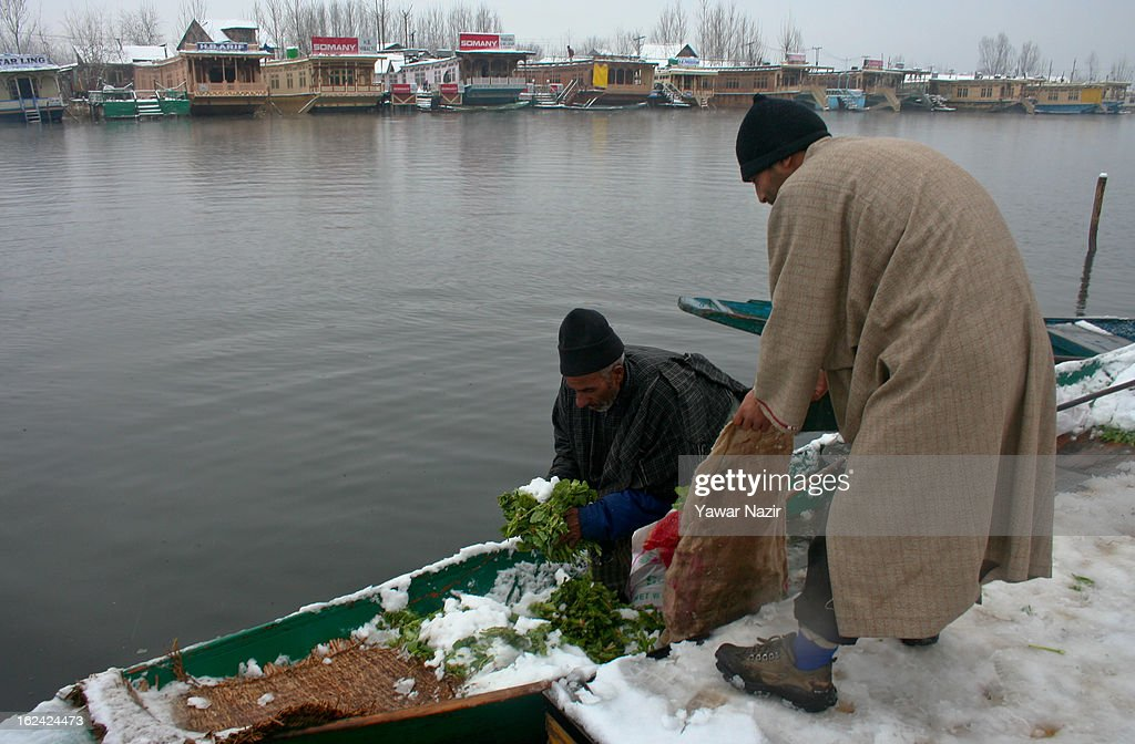Kashmiri men buy and sell vegetables on the bank of Dal lake after a snowfall on February 23, 2013 in Srinagar, Indian Administered Kashmir, India. Several parts of the Kashmir Valley, including the summer capital Srinagar, experienced fresh snowfall today, prompting the authorities to issue an avalanche warning and leading to closure of the Jammu-Srinagar Highway, the only road link between Kashmir and rest of India.
