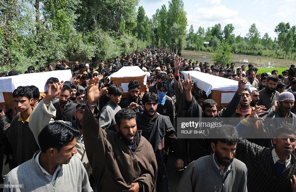 Kashmiri men carry the coffins of three civilians at the funeral procession in Rafiabad in northern Baramulla district on May 29, 2010. Police in Indian Kashmir fired teargas to disperse thousands of villagers protesting against what they said was the staged killing of three Muslims by the security forces. Late April, the military said it had foiled an infiltration bid by killing three militants along the de facto border that divides Kashmir between South Asian rivals India and Pakistan. But three families in the northern district of Baramulla said the slain men were 'innocent' relatives who had gone missing three days before. On May 28, authorities ordered a probe into the incident and also exhumed the three bodies, which were found to be those of the missing men. Thousands of villagers May 29 took to the streets of the men's home village in Baramulla, chanting: 'We want freedom' and 'Hang the killers'. AFP PHOTO/Rouf BHAT