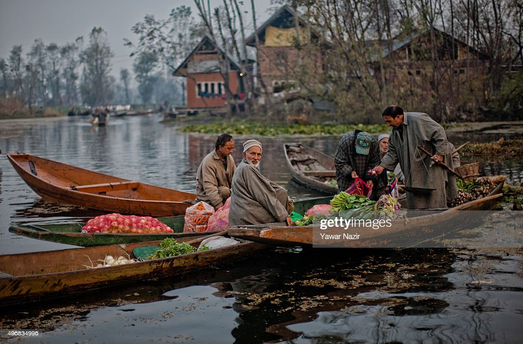 Kashmiri men gather with their boats laden with vegetables at the floating vegetable market on Dal Lake at dawn on November 12, 2015 in Srinagar, the summer capital of Indian administered Kashmir, India. The floating vegetable market at Guder, after remaining closed for many months due to last September's floods, is abuzz with activity again. Every morning Dal dwellers visit the market with their boats laden with vegetables that supply different parts of the city.