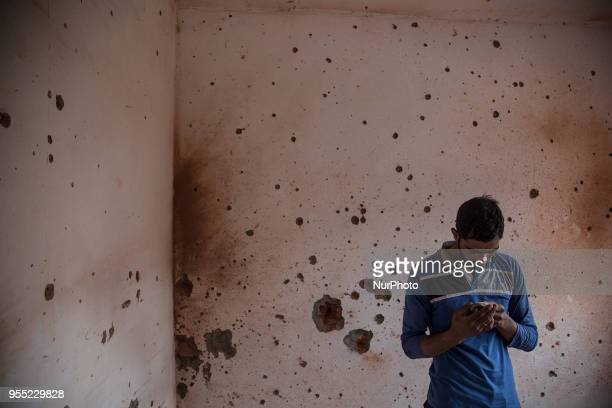 Kashmiri men inspect a house damaged during a gun fight where suspected rebels were holed up Saturday May 5 in Srinagar Indiancontrolled Kashmir...