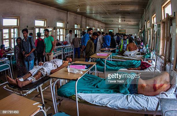 Kashmiri men lie injured on hospital bed after they were beaten by Indian government forces following violence that has left over 67 people dead and...