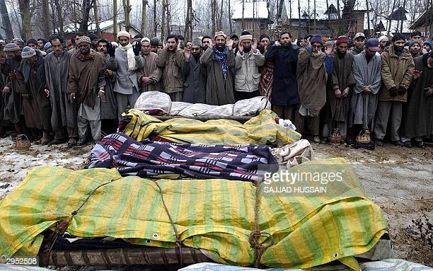 Kashmiri men raises their arms during prayers at the funeral of five civilians killed during a fierce encounter between Indian troops and Muslim...