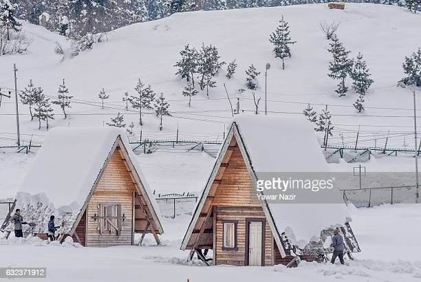 Kashmiri men remove snow from the huts after seasons first snowfall on January 22 2017 in Gulmarg to the west of Srinagar the summer capital of...