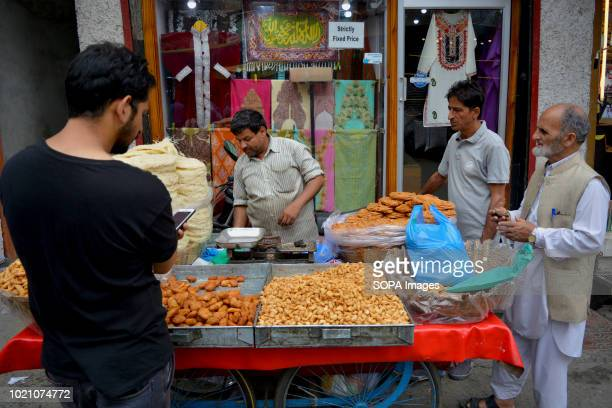 Kashmiri men seen buying from a road side vendor on the eve of Eid. Markets, bakeries, confectioneries and toy shops witnessed a heavy rush of...