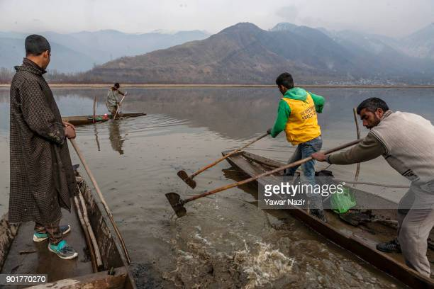 Kashmiri men thrash the water with oars to separate chestnut from the mud and weed on January 05 2018 in Kolhom north of Srinagar the summer capital...