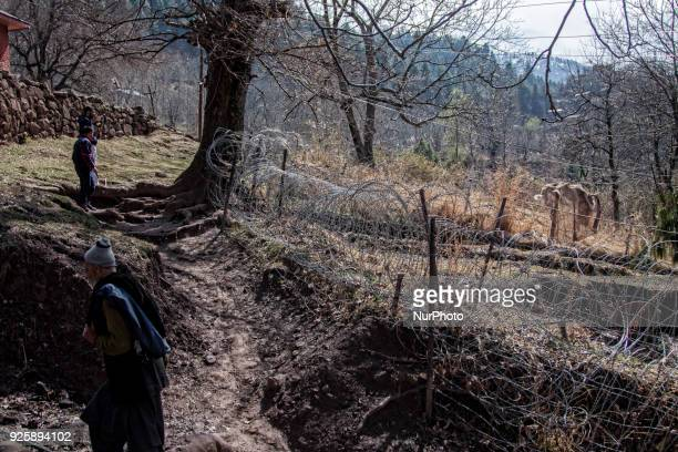 Kashmiri men walk in front the bunker of Indian army as they walk towards their abandoned home during a fresh skirmish along the border on February...