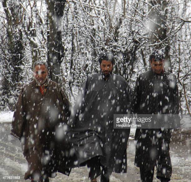 Kashmiri men walk through a snow covered road and trees on the outskirts of on March 10 2014 in Srinagar India Kashmir Valley including Srinagar city...