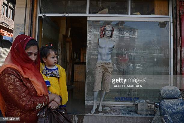 A Kashmiri mother and child walks past a shopfront as floodaffected residents clean up shops and residences following flooding in central Srinagar on...