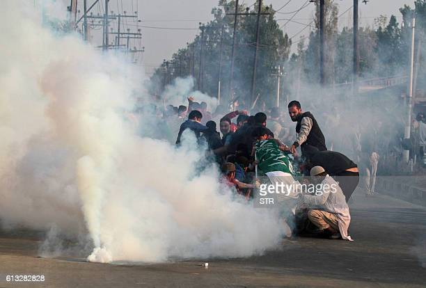 Kashmiri mourners hold the body of Junaid Ahmad as they are fired on with teargas by Indian police during his funeral procession in downtown Srinagar...