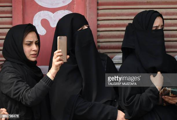 Kashmiri mourners look on during the funeral precession of militant Eisa Fazili in Srinagar on March 12 2018 Indian government forces killed three...
