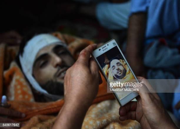 TOPSHOT Kashmiri mourners take photographs of the body of Burhan Muzaffar Wani the newage poster boy for the rebel movement in the restive Himalayan...