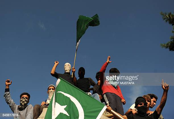 Kashmiri mourners wave the Pakistani flag as they shout profreedom slogans during the funeral of Burhan Muzaffar Wani the newage poster boy for the...