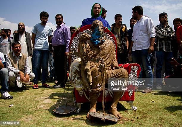 Kashmiri Muslim artist smeared with mud performs while the relatives of missing persons attend a protest demonstration for disappeared persons...