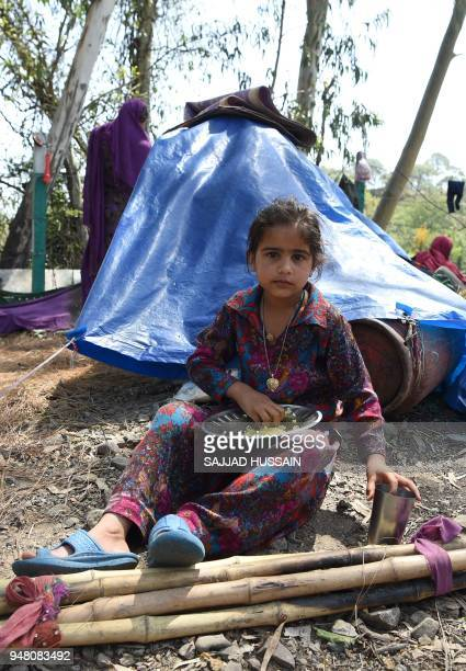 A Kashmiri Muslim Bakarwal nomad girl eats a meal at a temporary camp near Udhampur some 72 kms north of Jammu on April 18 2018 Nationwide protests...