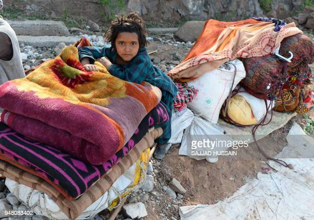 A Kashmiri Muslim Bakarwal nomad girl is pictured next to their possessions at a temporary camp near Udhampur some 72 kms north of Jammu on April 18...