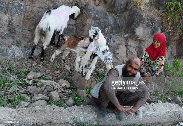 A Kashmiri Muslim Bakarwal nomad sits next to her daughter as goat play at their temporary camp near Udhampur some 72kms north of Jammu on April 18...