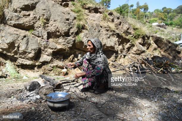 A Kashmiri Muslim Bakarwal nomad women prepares food at a temporary camp near Udhampur some 72 kms north of Jammu on April 18 2018 Nationwide...