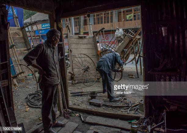Kashmiri Muslim blacksmiths make horse wagon wheels in a market on July 16 2018 in Budgam west of Srinagar the summer capital of Indian administered...