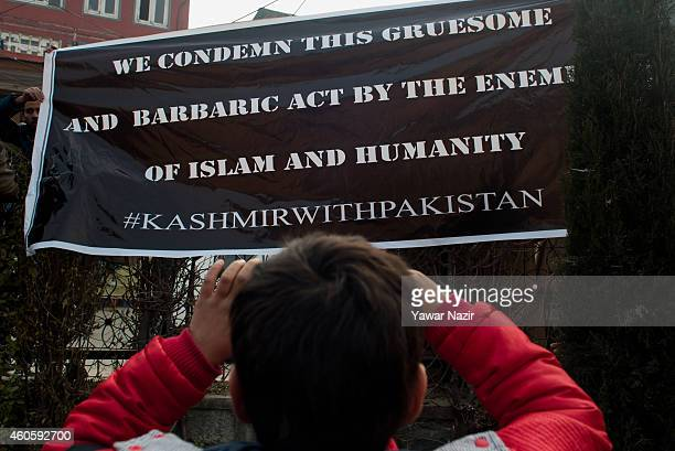 Kashmiri Muslim boy takes pictures of a banner hoisted on the wall of Grand Mosque for the victims killed in a militant attack in Peshawar in...