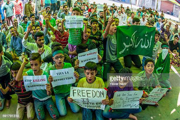 Kashmiri Muslim children hold placards as they shout anti Indian and pro Kashmir freedom slogans during an anti Indian protest following violence...