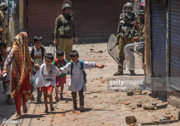Kashmiri Muslim children walk on the strewn stones thrown at Indian government forces by Kashmiri Muslim protesters during a protest after they...