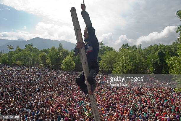 Kashmiri Muslim clims a pole to have a glimpse of Burhan Wan a top Hizb ul Mujahideen commander killed in a brief gun battle with Indian government...