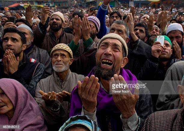 Kashmiri Muslim devotees look towards a cleric displaying the holy relic believed to be of Sufi Saint outside the Dastgeer Sahib shrine on the Friday...