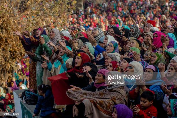 Kashmiri Muslim devotees look towards a cleric displaying the holy relic believed to be the whisker from the beard of the Prophet Mohammed at...