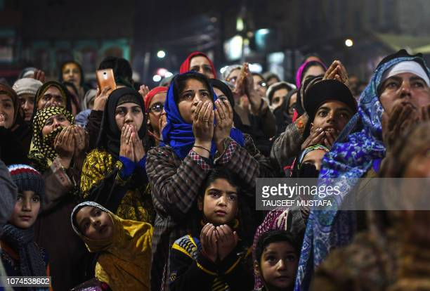 Kashmiri Muslim devotees pray as a priest displays a relic at the shrine ceremony of Sheikh Abdul Qadir Geelani in Srinagar on December 21 2018...