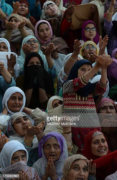 Kashmiri Muslim devotees pray as an unseen custodian displays a holy relic, believed to be a hair from the Prophet Muhammad's beard, at Kashmir's...