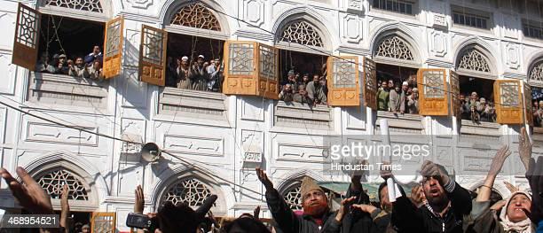 Kashmiri Muslim devotees pray as the head priest displays a relic of Sufi Saint Syed Abdul Qadir Jilani outside his shrine on February 12 2014 in...