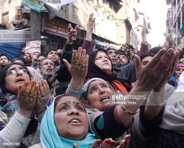 Kashmiri muslim devotees praying as the head priest displays a relic of Sufi Saint Syed Abdul Qadir Jilani outside his shrine on February 14 2014 in...
