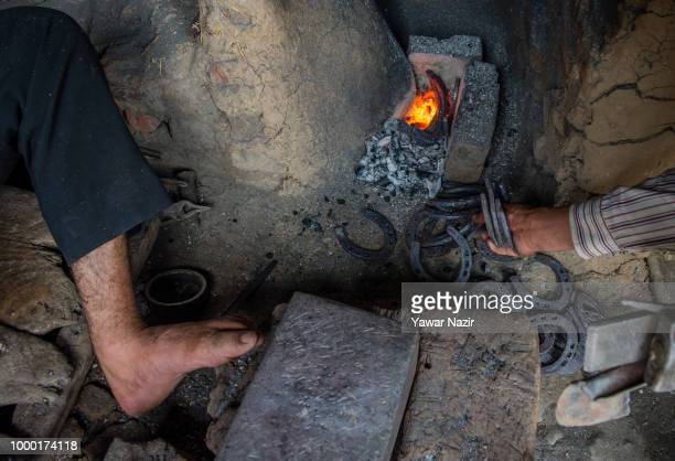 Kashmiri Muslim farriers make metal horse shoes in their workshop on July 16 2018 in Budgam west of Srinagar the summer capital of Indian...