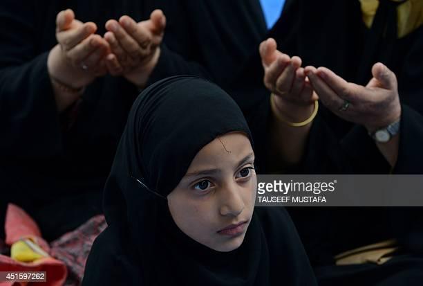 A Kashmiri Muslim girl looks on as women read the Koran Islam's holy book during the holy month of Ramadan at the Naqashband Sahib Shrine in Srinagar...