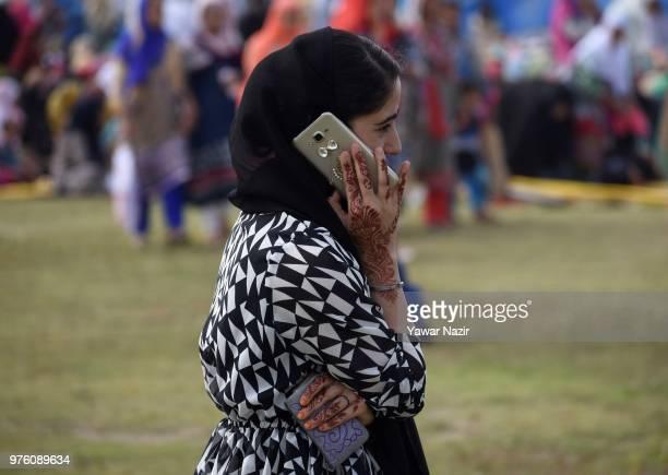 Kashmiri Muslim girl talks over phone as she waits for EidulFitr prayers at Eid Gah on EidulFitr a festival of Muslims on June 16 2018 in Srinagar...