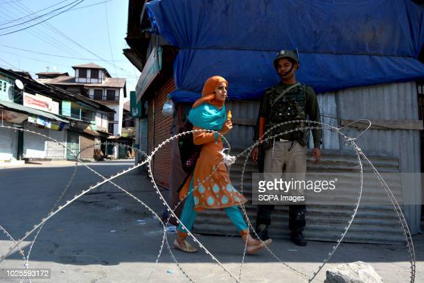 Kashmiri Muslim girl walks in front of a paramilitary trooper as he stands guard during the restriction in Downtown area of Srinagar the summer...