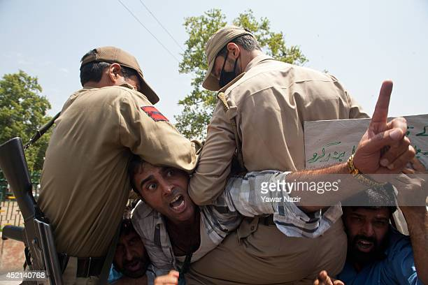 Kashmiri Muslim government employee shouts anti Israeli slogans after being detained by Indian during a protest against Israel's military operation...