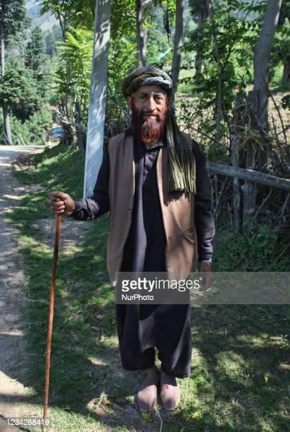 Kashmiri Muslim Gujjar man walks along a small village pathway in Kanchnambal, Kashmir, India, on June 23, 2010.