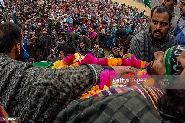 Kashmiri Muslim look towards the body of Rayees Ahmad a militant who was killed in a gun battle with the Indian government forces during his funeral...