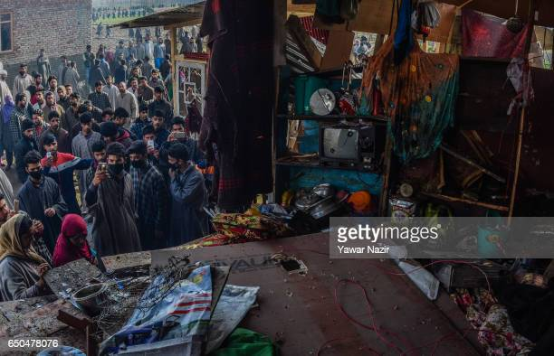 Kashmiri Muslim look towards the debris of war ravaged residential house after a gun battle between Indian government forces and Kashmiri rebels on...