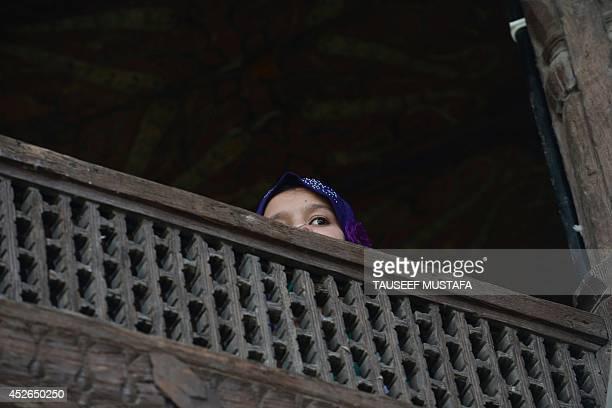 A Kashmiri Muslim looks on after offering JummatulVida the last congregational Friday prayers in the holy month of Ramadan at the ShahiHamdaan shrine...