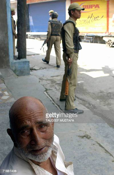 Kashmiri Muslim looks on as Indian Central Reserve Police Force soldiers stand alert during a cordon and search operation at Kukar Bazar in Srinagar,...