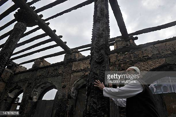 A Kashmiri Muslim man cries as he touches the ruins of a revered 200year old sufi shrine in downtown Srinagar on July 5which was gutted in a devasted...