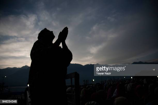 Kashmiri Muslim man is silhouetted against the sky as he prays while a Muslim cleric displays the holy relic believed to be the whisker from the...