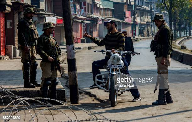 Kashmiri Muslim man pleads Indian paramilitary troopers to let him pass the concertina wire during a strike on October 27 2017 in Srinagar the summer...