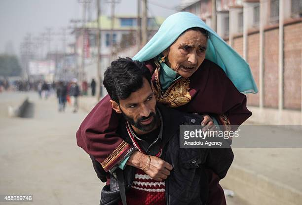 Kashmiri Muslim man takes her mother to a nearby hospital on his shoulders during strict restrictions imposed by government to thwart any religious...
