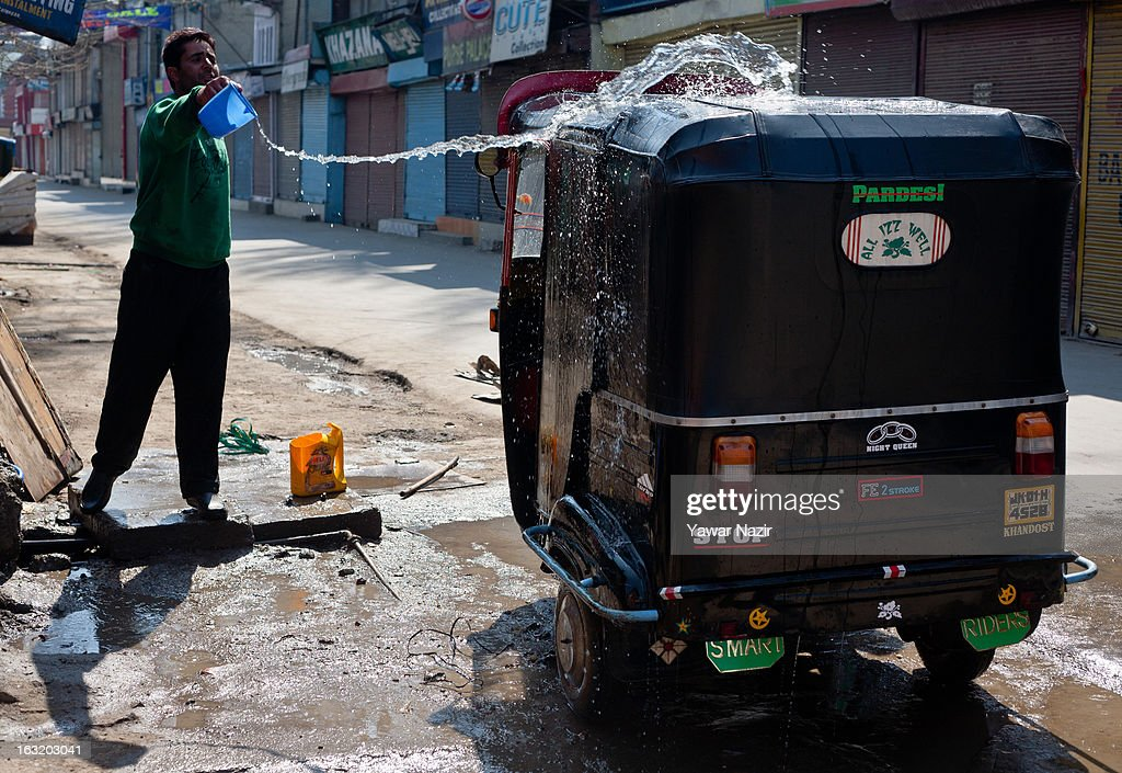 A Kashmiri Muslim man washes his rickshaw during a curfew like restriction on March 06, 2013 in Srinagar, the summer capital of Indian Administered Kashmir, India. Indian authorities imposed curfew like restrictions in most parts of Kashmir following a killing of kashmiri youth by Indian army in North Kashmir's Baramulla district yesterday.