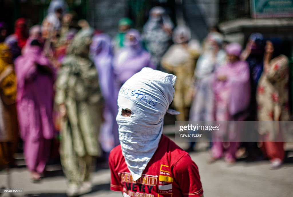 A Kashmiri Muslim masked protester stands in front the women protesters shouting anti Indian and pro Kashmir Independence slogans during a protest, following weeks of violence that has left over 50 people dead and thousands injured, on July 28, 2016 in Srinagar, the summer capital of Indian administered Kashmir, India. Indian government forces used teargas shells and canisters to disperse thousands of Kashmiri Muslim protesters in Srinagar. Fierce protests in Indian-administered Kashmir over the killing of a young rebel commander Burhan Wani have left over 50 people dead and over 3000 as an ongoing unrest in Indian controlled Kashmir enters its 19th day. It is the worst violence in the area since 2010. The protests have triggered a heavy crackdown by Indian government forces including many strict curfews.